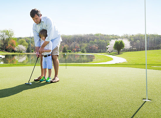 man playing golf with child